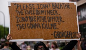 """MINNEAPOLIS, MN - MAY 26: A protester holds a sign while demonstrating against the death of George Floyd outside the 3rd Precinct Police Precinct on May 26, 2020 in Minneapolis, Minnesota. Four Minneapolis police officers have been fired after a video taken by a bystander was posted on social media showing Floyd's neck being pinned to the ground by an officer as he repeatedly said, """"I can't breathe"""". Floyd was later pronounced dead while in police custody after being transported to Hennepin County Medical Center. (Photo by"""