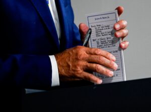 "TOPSHOT - US Presidential candidate and former Vice President, Joe Biden holds a pad with potential Vice Presidential names on it and other notes, during a campaign event at the William ""Hicks"" Anderson Community Center in Wilmington, Delaware on July 28, 2020. (Photo by ANDREW CABALLERO-REYNOLDS / AFP) (Photo by"
